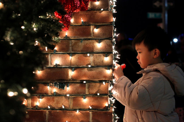 A child looks at the illuminations at the Dyker Heights Christmas Lights in the Dyker Heights neighborhood of Brooklyn, New York City, U.S., December 23, 2016. (Photo by Andrew Kelly/Reuters)
