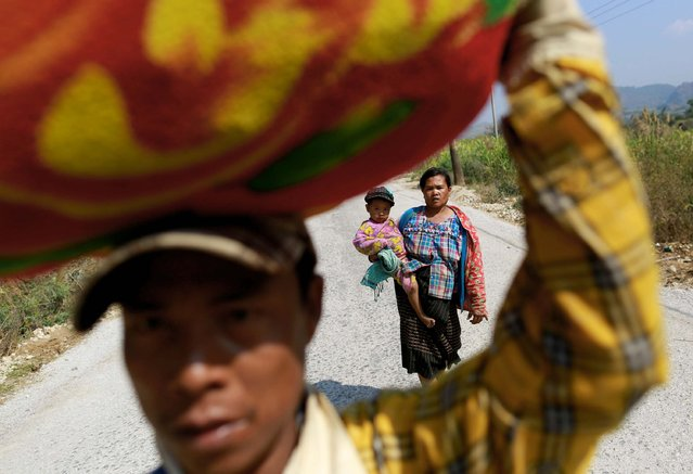 A family displaced by recent violence, walks down a road, in Laukkai February 17, 2015. (Photo by Soe Zeya Tun/Reuters)