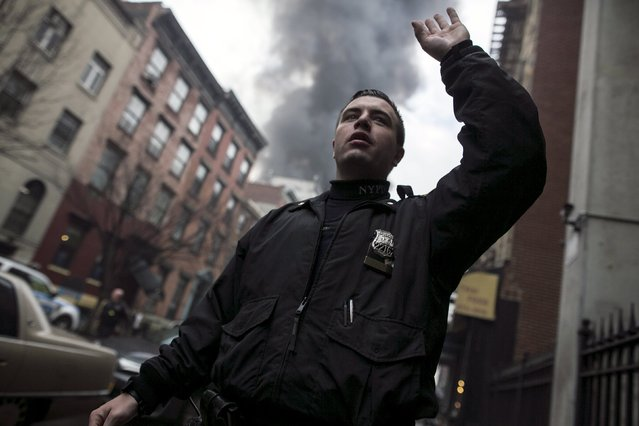 A New York Police Department (NYPD) signals residents way from the site of a building fire in the East Village neighborhood of New York City on March 26, 2015. (Photo by Ben Hider/Reuters)