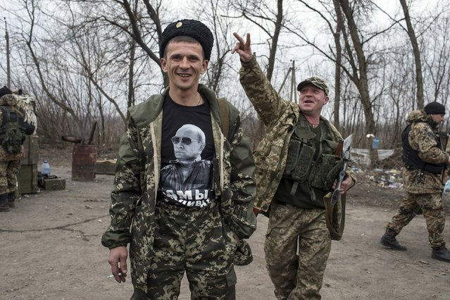 A pro-Russian rebel shows his t-shirt depicting Russian President Vladimir Putin at a checkpoint in the village of Chornukhyne near the town of Debaltseve, north-east from Donetsk, March 12, 2015. (Photo by Marko Djurica/Reuters)