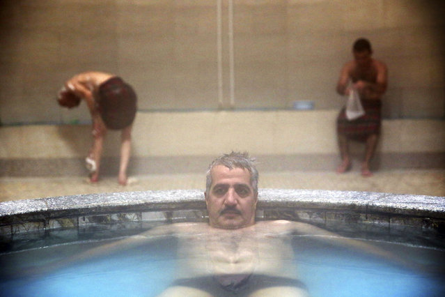 In this October 15, 2014 photo, a man lies in a small pool at the Nezafat public bathhouse, in Tabriz, Iran. (Photo by Ebrahim Noroozi/AP Photo)