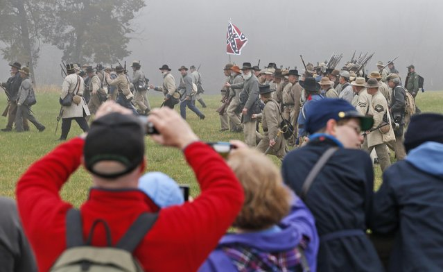 Confederate troops charge advancing Union troops as visitors watch during a re-enactment of the Battle of Appomattox Courthouse as part of  commemoration of the 150th anniversary of the surrender of the army of Northern Virginia at Appomattox Court House in Appomattox, Va., Thursday, April 9, 2015. (Photo by Steve Helber/AP Photo)