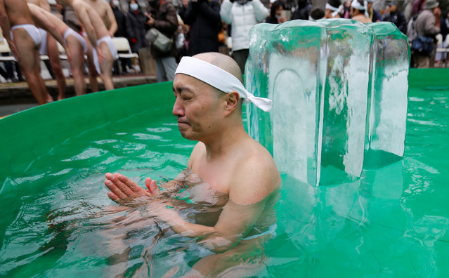 """A man wearing the traditional """"fundoshi"""" or loin cloth prays as he bathes in ice-cold water outside the Teppozu Inari shrine in Tokyo, Japan, January 8, 2017. (Photo by Toru Hanai/Reuters)"""