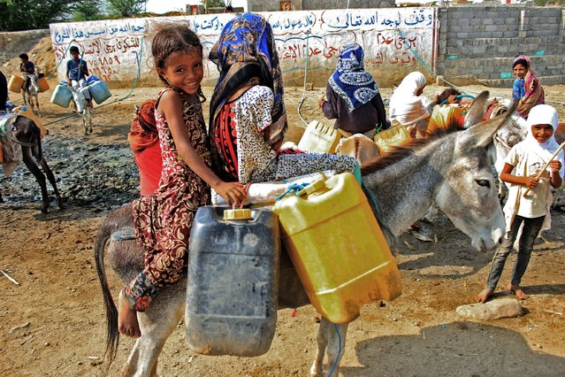 Children riding on donkeys queue to fill their jerrycans with water from a cistern at a make-shift camp for the internally displaced in Yemen's northern Hajjah province on July 12, 2021, amidst an extreme heat wave and severe water shortage. (Photo by Essa Ahmed/AFP Photo)