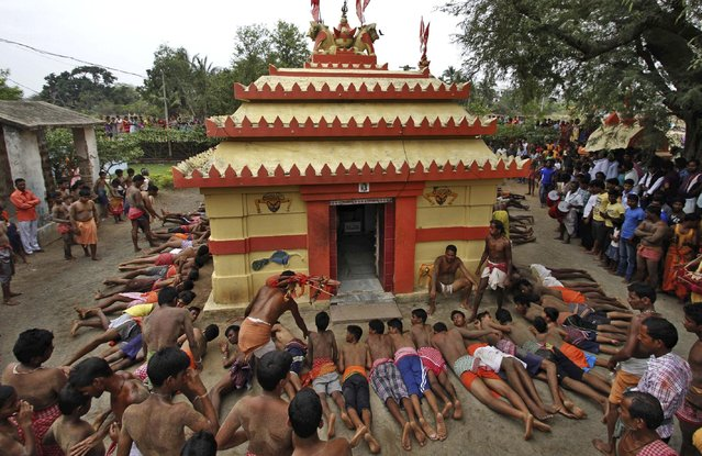 Indian men roll on hot sand around their village goddess temple as they perform a ritual during their annual Jhamu Yatra festival at Mendhasala village, outskirts of Bhubaneswar, India, Monday, April 13, 2015. (Photo by Biswaranjan Rout/AP Photo)