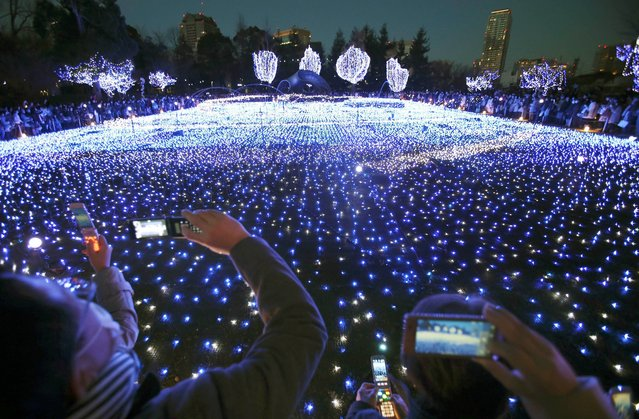 Visitors take a picture of Christmas illuminations, lit by 280,000 LED lights, at Tokyo Midtown business and commercial complex in Tokyo, Saturday, December 21, 2013. (Photo by Koji Sasahara/AP Photo)