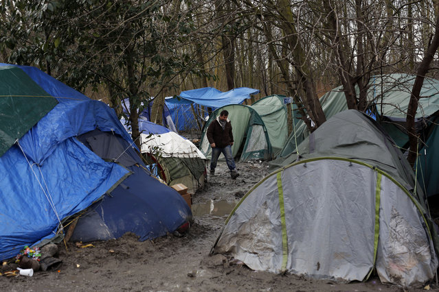 """A migrant walks in the mud in a makeshift camp where over 1,000 migrants mostly from Iraqi Kurdistan live in Grand-Synthe, near the northern town of Dunkerque, France, February 24, 2016. The clock is ticking for hundreds of migrants in the nearby port city of Calais waiting for a judge to decide whether to postpone an eviction order in the camp locally referred to as """"the jungle"""". (Photo by Jerome Delay/AP Photo)"""