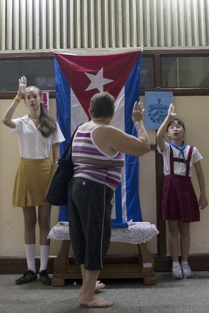School girls salute as a woman casts her vote at a polling station in Havana April 19, 2015. (Photo by Alexandre Meneghini/Reuters)