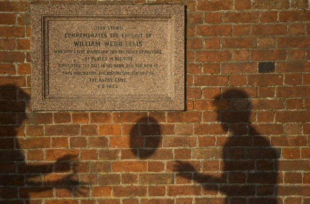 The shadows of pupils throwing a ball are cast near a plaque dedicated to William Web Ellis as they pose for another photographer at Rugby school in central England, January 20, 2015. (Photo by Neil Hall/Reuters)