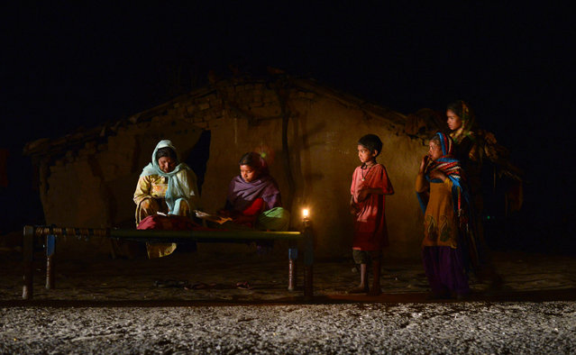 An Indian girl (C) studies by candle light in a slum area without electric power in Phillaur, around 50 km from Jalandhar, on February 29, 2016. India's government will work to ensure all the country's villages have electricity within two years, Finance Minister Arun Jaitley said, as he presented the annual budget on February 29. (Photo by Shammi Mehra/AFP Photo)