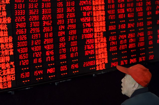 "An investor looks at an electronic board showing stock information at a brokerage house in Taiyuan, Shanxi province April 21, 2015. China stocks jumped on Tuesday as bullish investors piled into small-cap stocks, betting on further gains despite stretched valuations and a warning from official Xinhua News Agency against ""irrational exuberance"". (Photo by Jon Woo/Reuters)"