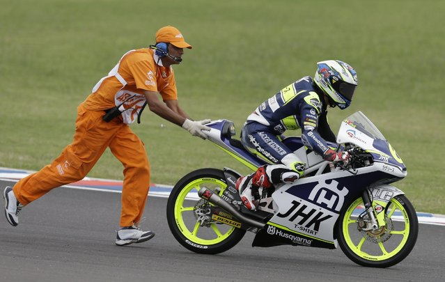A race official pushes the Husqvarna of Spain's Maria Herrera after she fell during the Moto3 race of the Argentina's Motorcycle Grand Prix at the Termas de Rio Hondo circuit in Argentina, Sunday, April 19, 2015. (Photo by Natacha Pisarenko/AP Photo)