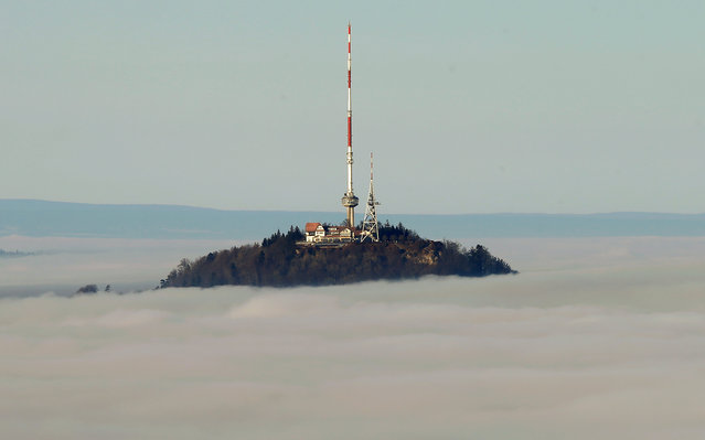 Fog covers the landscape around the peak of Uetliberg mountain (869m/2,850 feet above sea level) in Zurich, Switzerland December 21, 2016. (Photo by Arnd Wiegmann/Reuters)