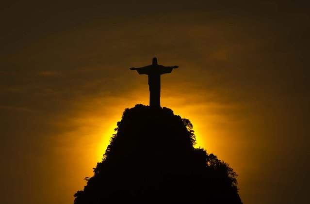 The sun sets behind the Christ the Redeemer statue and the Corcovado mountain on December 28, 2012. (Photo by Felipe Dana/Associated Press)