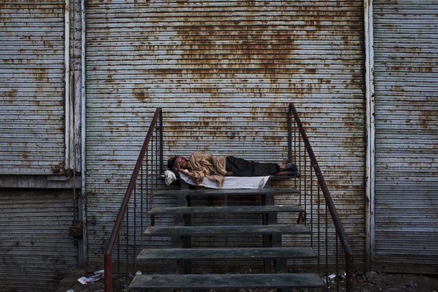 A homeless man sleeps outside shops with their shutter down New Delhi, India, Thursday, April 16, 2015. The International Monetary Fund (IMF) and the World Bank have forecast India's growth to rise up to 7.5 per cent next fiscal, overtaking China as the fastest growing emerging economy in 2015-16. (Photo by Bernat Armangue/AP Photo)