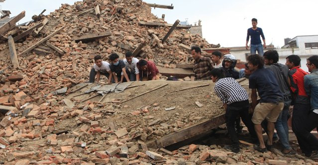 In this April 25, 2015 photo, people try to lift the debris from a temple at Hanumandhoka Durbar Square after an earthquake in Kathmandu, capital of Nepal, Saturday, April 25, 2015. (Photo by Sunil Sharma/Xinhua via AP Photo)
