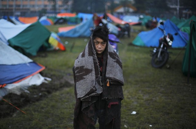 A boy wraps himself with blankets as he stands outside his makeshift shelter at open ground in the early hours, following the April 25 earthquake in Kathmandu, Nepal April 29, 2015. (Photo by Adnan Abidi/Reuters)