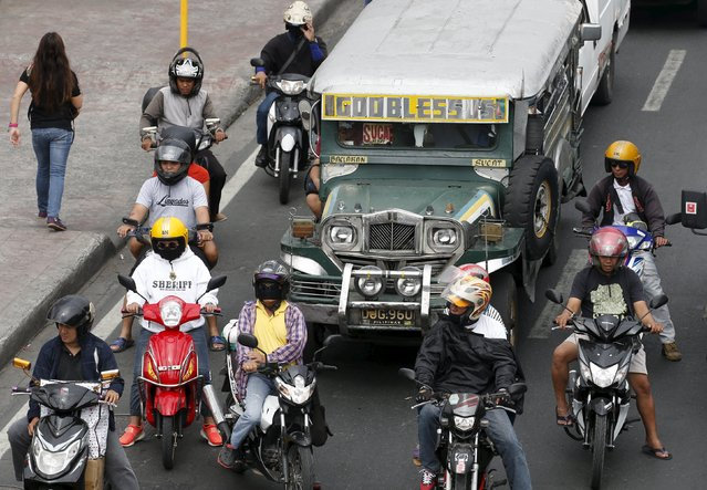 Motorcycle motorists and a public transport jeepney are pictured as they wait for the greenlight of a traffic light (not pictured) along a road in Paranaque, Metro Manila March 2, 2016. (Photo by Erik De Castro/Reuters)