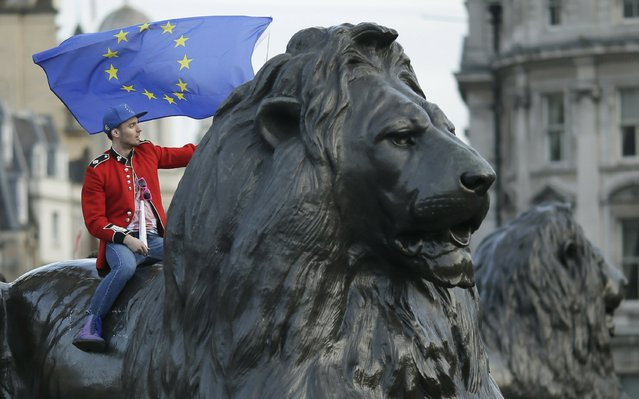 A demonstrator sits on one of the lions in Trafalgar Square during a Peoples Vote anti-Brexit march in London, Saturday, March 23, 2019. The march, organized by the People's Vote campaign is calling for a final vote on any proposed Brexit deal. This week the EU has granted Britain's Prime Minister Theresa May a delay to the Brexit process. (Photo by Tim Ireland/AP Photo)