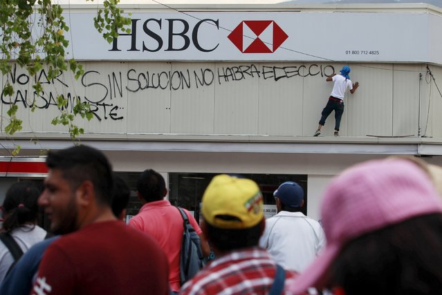 "A protester spray-paints slogans on the wall of a HSBC bank branch during a march for Labour Day in Chilpancingo, Mexico May 1, 2015. The slogan the man is currently spray-painting reads, ""Without solution, there will be no election"". (Photo by Daniel Becerril/Reuters)"