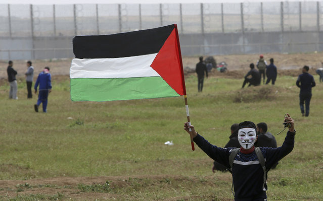 A masked protester waves his national flag near the fence of the Gaza Strip border with Israel, marking first anniversary of Gaza border protests east of Gaza City, Saturday, March 30, 2019.  Tens of thousands of Palestinians gathered Saturday at rallying points near the Israeli border to mark the first anniversary of weekly protests in the Gaza Strip, as Israeli troops fired tear gas and opened fire at small crowds of activists who approached the border fence. (Photo by Adel Hana/AP Photo)