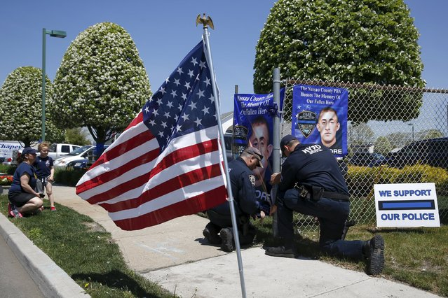 Police officers hang a banner honoring NYPD officer Brian Moore outside his wake at the Fredrick J. Chapey and Sons Funeral Home in Bethpage, New York, May 7, 2015. (Photo by Shannon Stapleton/Reuters)