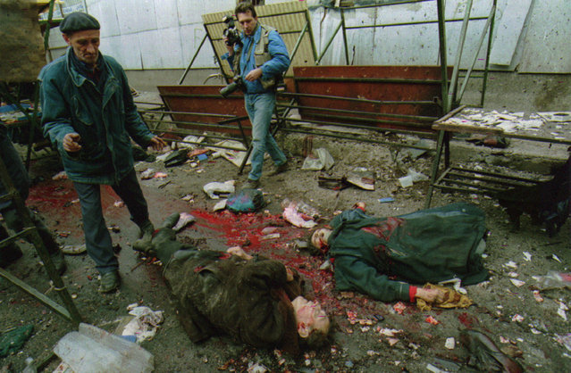 An elderly man and a photographer view two bodies of some 60 people killed by a mortar attack on Sarajevo's central market, February 1994. (Photo by Corinne Dufka/Reuters)