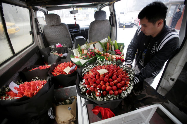 A delivery staff of a florist places a bouquet made of strawberries and flowers, priced at 450RMB, on Valentine's Day in Beijing, China, February 14, 2017. (Photo by Jason Lee/Reuters)