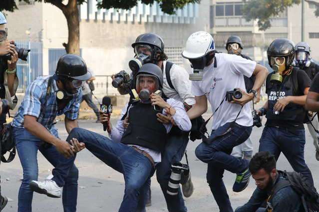 Journalists help reporter Gregory Jaimes, holding a VPITV microphone, who was injured while covering clashes between security forces and anti-government protesters in the Altamira neighborhood of Caracas, Venezuela, Wednesday, May 1, 2019. (Photo by Ariana Cubillos/AP Photo)