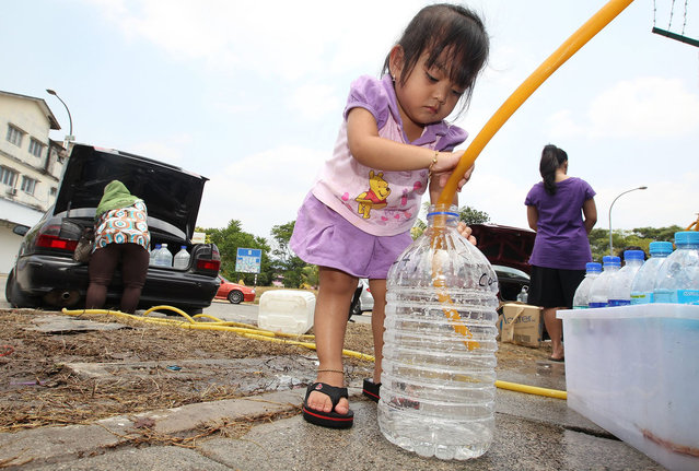 NurNisa Yasmin Mohd Fadzil, 3, the youngest of three siblings, helps her mother, Suhaila Zakaria, 35, fill water into a bottle in Balakong, Selangor, Malaysia on February 26, 2014. (Photo by Norafifi Ehsan/The Star)