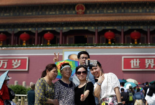 A Chinese family member uses a selfie stick to take a photo of themselves in front of Tiananmen Gate in Beijing, China, Thursday, April 30, 2015. Selfie sticks are gaining popularity in China, and many people are using them at popular tourist destinations. (Photo by Andy Wong/AP Photo)