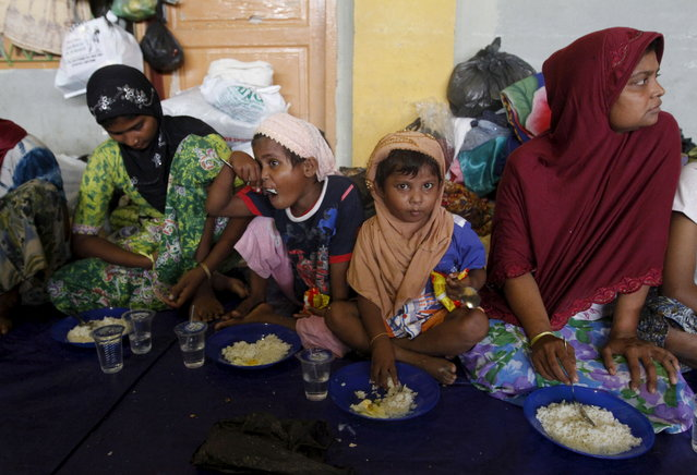 Migrants believed to be Rohingya take their breakfast inside a shelter after being rescued from boats at Lhoksukon, in Indonesia's Aceh Province May 12, 2015. Thailand and Malaysia may set up camps and detention centers to shelter hundreds of refugees arriving on their shores, officials said on Tuesday, as a leading inter-governmental agency said about 7,000 boatpeople were still adrift in the Bay of Bengal. (Photo by Roni Bintang/Reuters)