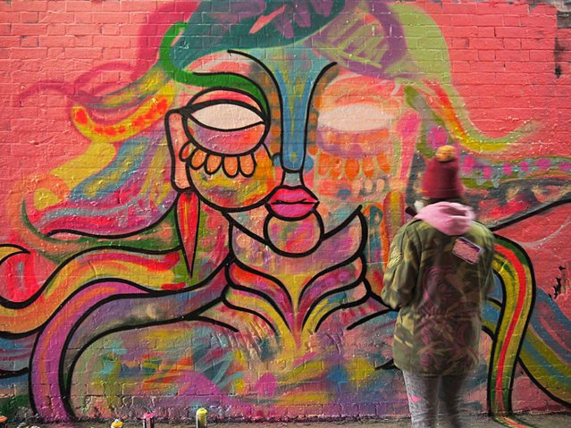 Amara Por Dios adds to the Leake Street Tunnel mural. (Photo by Dez Mighty/Susan Mackey)