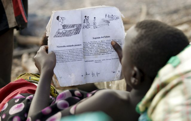 A Burundian refugee child reads a book on the shores of Lake Tanganyika in Kagunga village in Kigoma region in western Tanzania, as they wait for MV Liemba to transport them to Kigoma township, May 18, 2015. (Photo by Thomas Mukoya/Reuters)