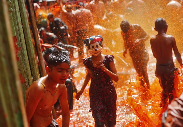 "A girl wearing a mask runs as boys splash coloured water on her during ""Huranga"" at Dauji temple, near the northern Indian city of Mathura March 18, 2014. Huranga is a game played between men and women a day after Holi, the festival of colours, during which men drench women with liquid colours and women tear off the clothes of the men. (Photo by Anindito Mukherjee/Reuters)"