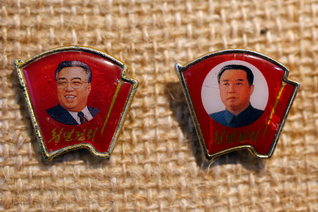 Two pins featuring former North Korean leader Kim Il Sung wearing different facial expressions are displayed in a glass case of Thomas Hui at his apartment in Hong Kong, China April 11, 2016. Collector Thomas Hui, 37, a former bank employee in Hong Kong, who is fascinated by North Korean pins and badges, has gathered over 100 featuring former leaders Kim Il Sung and Kim Jong Il, and has been buying and trading these Communist accessories since 2008. (Photo by Bobby Yip/Reuters)