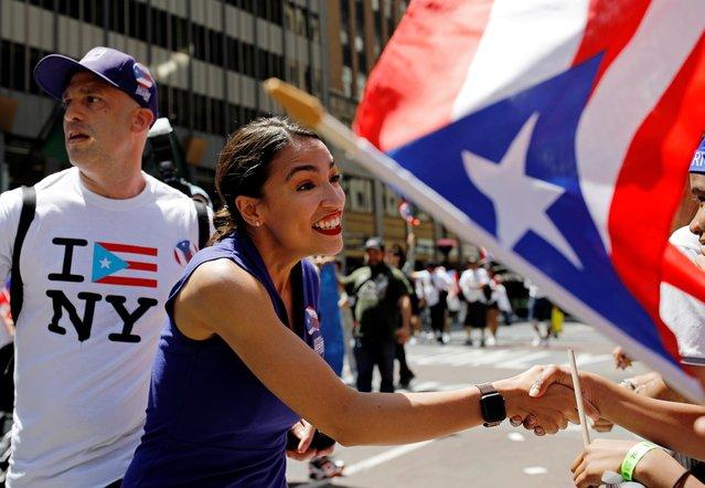 Representative Alexandria Ocasio-Cortez shakes hands on 5th Avenue at the annual Puerto Rican Day Parade in Manhattan, New York, U.S. June 9, 2019. (Photo by Jose Alvarado Jr./Reuters)