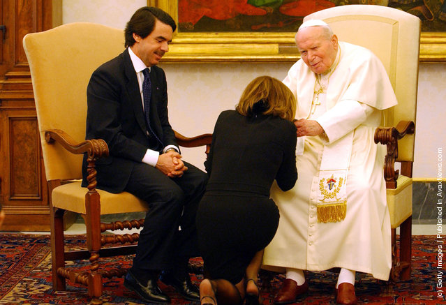 Spanish Prime Minister Jose Maria Aznar watches as his wife, Spanish First Lady Ana Botella Aznar, kneals before Pope John Paul II