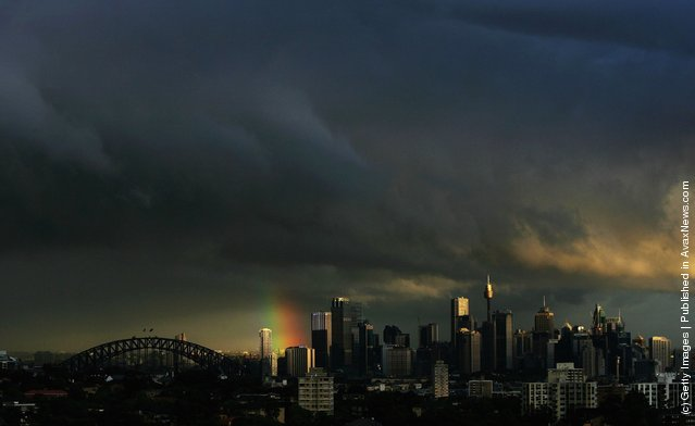 A rainbow appears over the Sydney Harbour Bridge (L) as storm clouds gather over the city skyline at sunset July 20, 2006 in Sydney, Australia