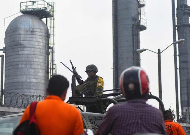 A soldier stands guard atop a vehicle while blocking the access to Mexican national oil company Pemex's Pajaritos petrochemical complex in Coatzacoalcos, Veracruz state, Mexico, April 21, 2016. (Photo by Angel Hernandez/Reuters)
