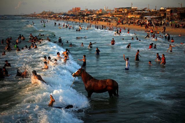 A Palestinian man washes his horse in the waters of the Mediterranean Sea as people swim on a hot day in the northern Gaza Strip on June 18, 2019. (Photo by Mohammed Salem/Reuters)