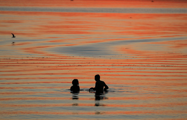 People enjoy sunset in a lake on the outskirts of Minsk, Belarus on June 4, 2019. (Photo by Vasily Fedosenko/Reuters)