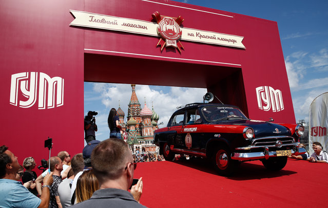 A Militsiya vintage car during the 2019 GUM Motor Rally featuring classic cars in Moscow, Russia on July 28, 2019. The Spasskaya Tower clock signals the start of the rally, when 120 cars traverse the route. The main objective is to maintain the required speed and reach the control points on time. (Photo by Artyom Geodakyan/TASS via Getty Images)