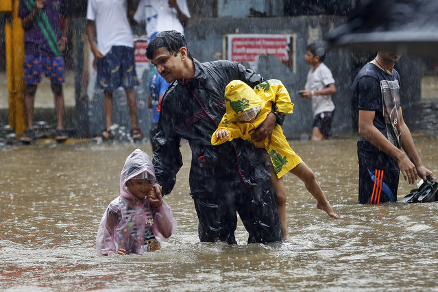 An Indian man carries children and crosses a waterlogged street as it rains in Mumbai, India, Friday, June 19, 2015. (Photo by Rajanish Kakade/AP Photo)