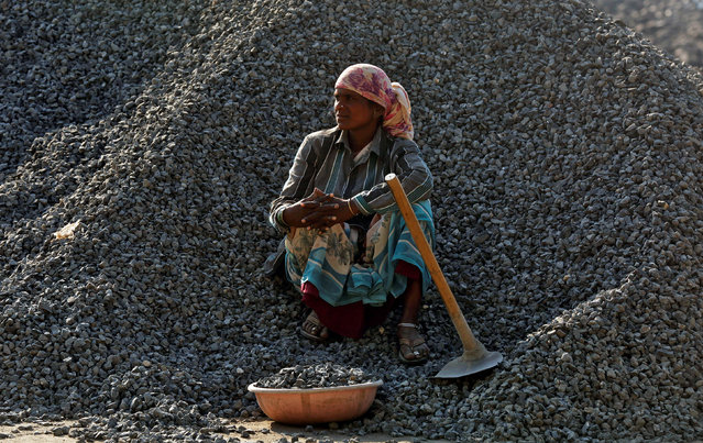 A woman labourer rests on a pile of stones at a construction site, in Mumbai, March 16, 2017. (Photo by Shailesh Andrade/Reuters)
