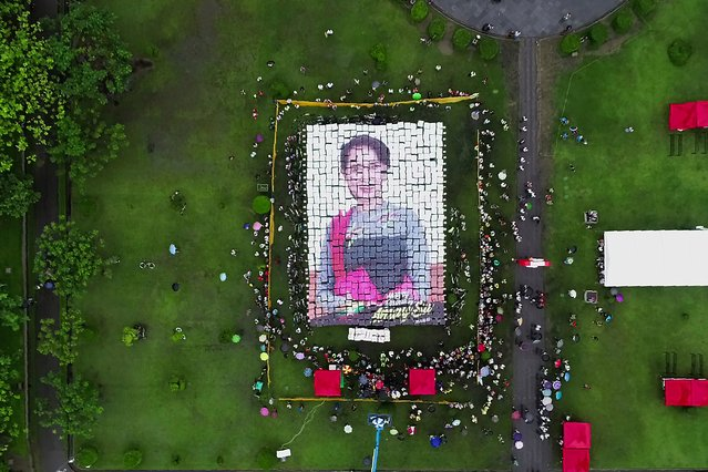 This aerial handout picture taken and provided on June 19, 2019 by one of the event organizers, Tharr Zaw, shows supporters making a mosaic portrait of Myanmar State Counsellor Aung San Suu Kyi with placards during an event to celebrate her 74th birthday in Yangon. (Photo by Tharr Zaw/AFP Photo)