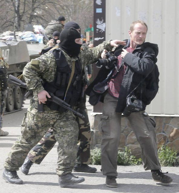 Masked pro-Russian gunmen attack a photojournalist near combat vehicles flying a Russian flag, in downtown of Slovyansk on Wednesday, April 16, 2014. The troops on those vehicles wore green camouflage uniforms, had automatic weapons and grenade launchers and at least one had the St. George ribbon attached to his uniform, which has become a symbol of the pro-Russian insurgency in eastern Ukraine. (Photo by Efrem Lukatsky/AP Photo)