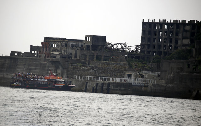 "In this June 29, 2015 photo, a tourist boat arrives at Hashima Island, commonly known as Gunkanjima, which means ""Battleship Island"", off Nagasaki, Nagasaki Prefecture, southern Japan. The island is one of 23 old industrial facilities seeking UNESCO's recognition as world heritage ""Sites of Japan's Meiji Industrial Revolution"" meant to illustrate Japan's rapid transformation from a feudal farming society into an industrial power at the end of the 19th century. (Photo by Eugene Hoshiko/AP Photo)"