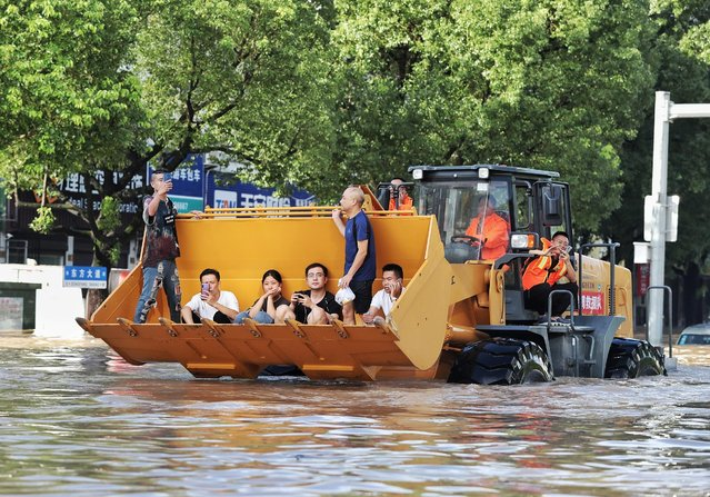 Rescue workers evacuate stranded residents with a bulldozer on a flooded street after typhoon Lekima hit Taizhou, Zhejiang province, China on August 11, 2019. (Photo by Reuters/China Stringer Network)
