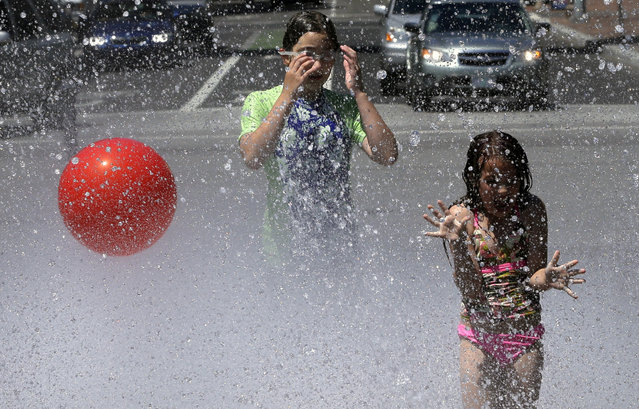 Children play in the Salmon Street Springs fountain in Portland, Ore., Wednesday, July 1, 2015. A heat advisory is in effect for Portland from noon Wednesday to 8 p.m. Thursday, according to the national weather service. (Photo by Don Ryan/AP Photo)